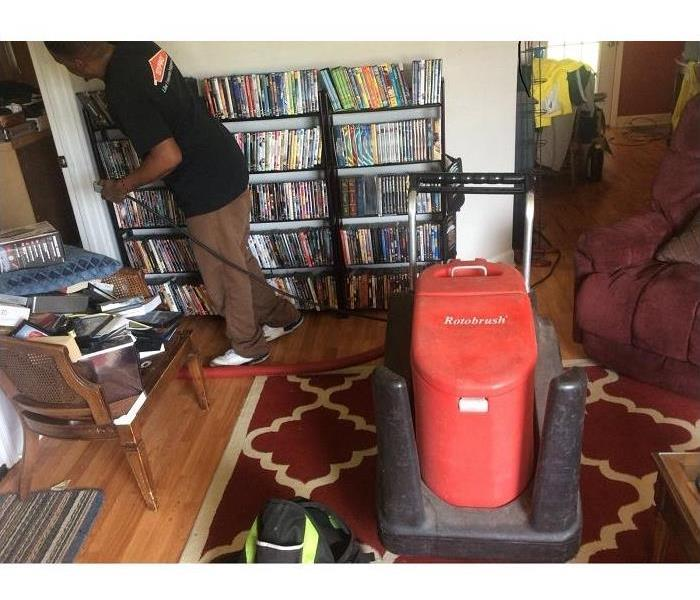 SERVPRO employee, den living area with home owners contents, red rotobrush to clean ducts
